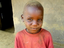 Joshua is a little boy who's mother was a former child soldier but died of HIV. This photo was taken in his village but now this sweet orphaned boy has a home at a boarding school in Lira.
